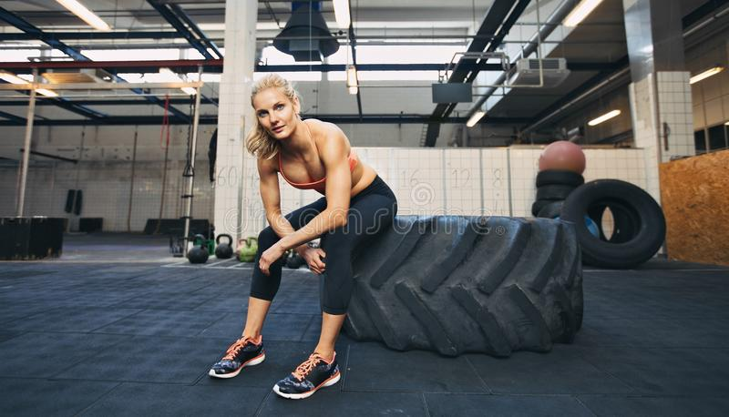 Crossfit woman taking break at gym. Beautiful and strong young woman sitting on a big tire after her exercise. Woman taking break after crossfit workout at gym stock photo