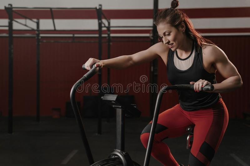Crossfit woman using exercise bike at the gym. Fitness female using air bike for cardio workout at gym. Copy space stock photo