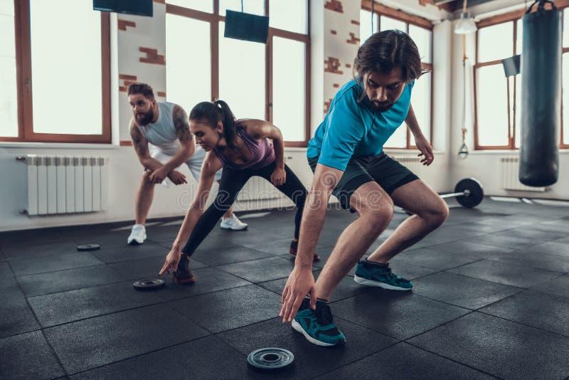 Crossfitatleten wat betreft Barbell-Gewicht in Gymnastiek stock fotografie