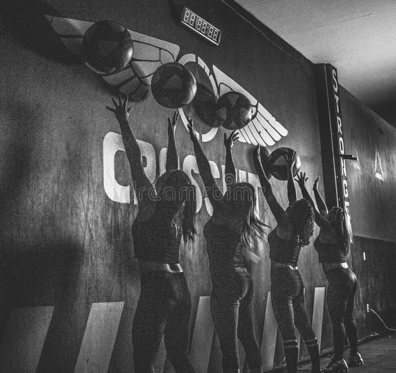 Crossfitters formant des silouettes quotidiens durs de wod noirs et blancs photographie stock libre de droits