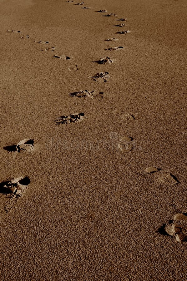 Crossing footprints in sand royalty free stock photos