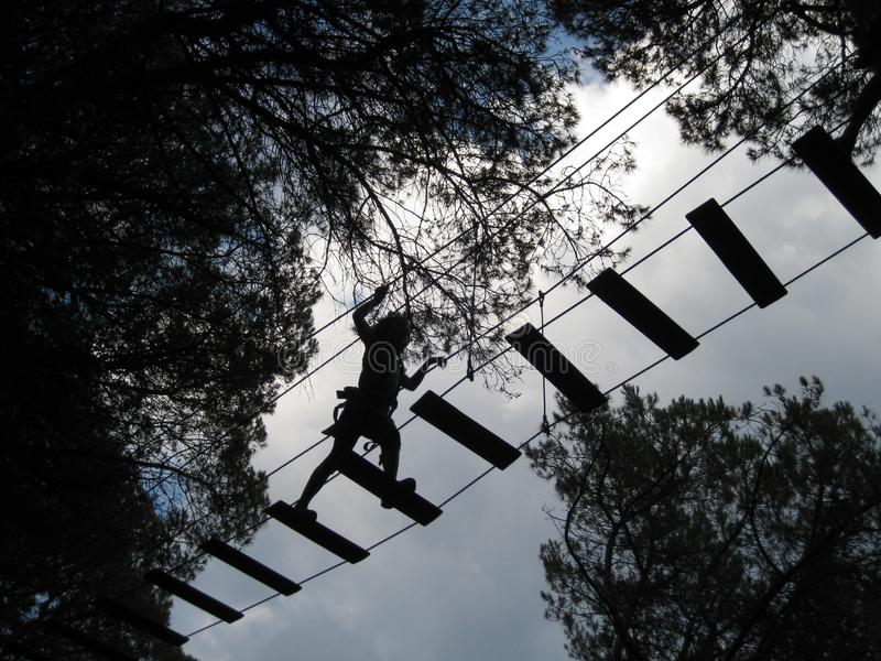 Crossing a gangway between trees in an adventure park when it& x27;s dark stock image