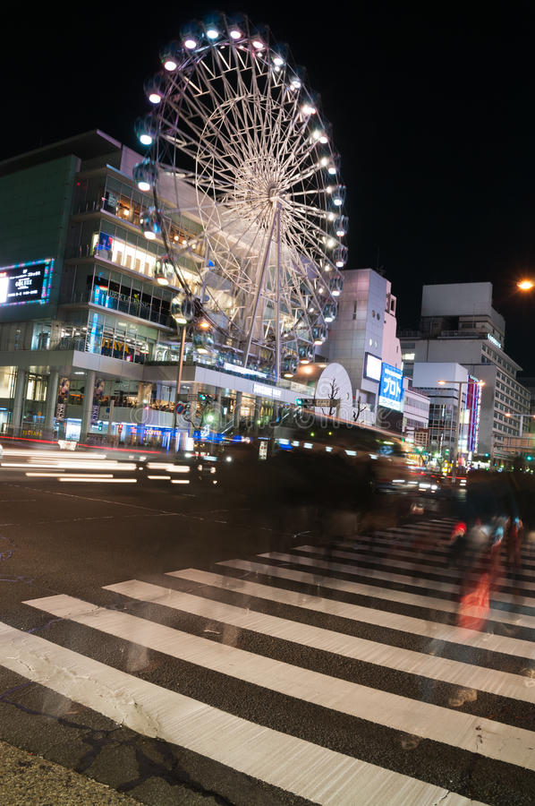Crossing at night in front of the Sunshine Sakae building Nagoya, Japan. Pedestrians appear as ghosts on the crossing in front of the Ferris Wheel of the stock photo