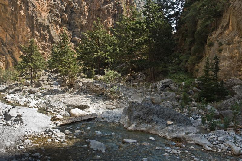 Crossing over mountain river at rocky terrain of Samaria gorge, south west part of Crete island. Greece royalty free stock images