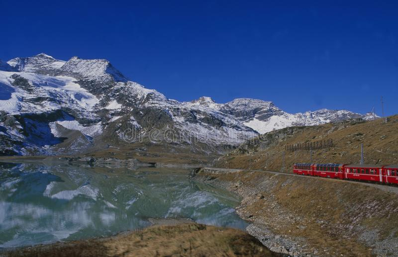 Crossing the swiss alps via Train trip at Lago Bianco,. Switzerland: Train trip with Rhätische Bahn through the swiss alps at Lago Bianco on Bernina Pass stock photography