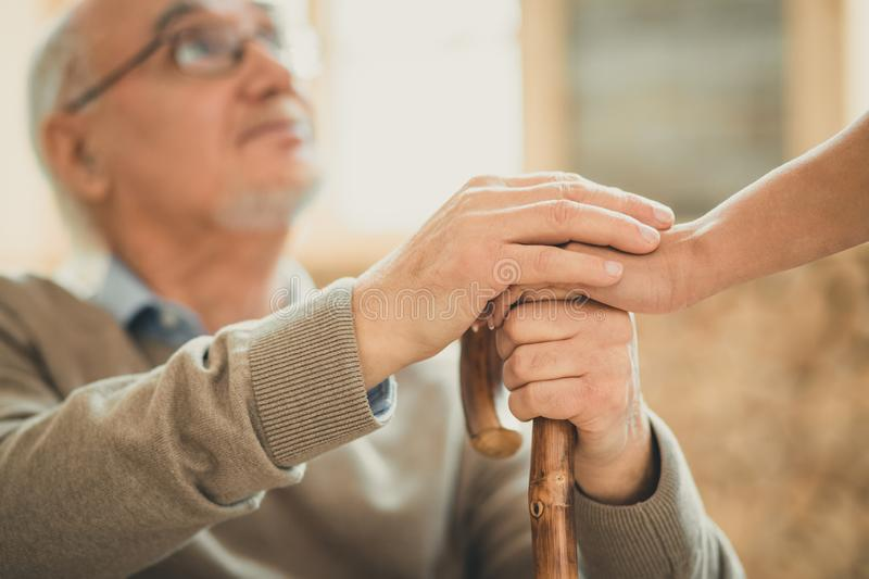 Afraid old man looking on his nurse with hope. Crossing their hands. Afraid old men looking on his nurse with hope while she holding his hand settling down royalty free stock photo