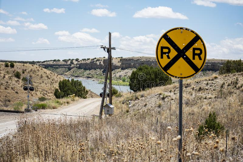 Crossing the Tracks. Image with Rail Road signage and tracks. Utility pole and cables. Bullet-holes in sign, help with semi- rustic look. The brpwn and tan of stock photos