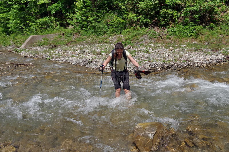 Mountain river. Young woman crossing the cold water royalty free stock image