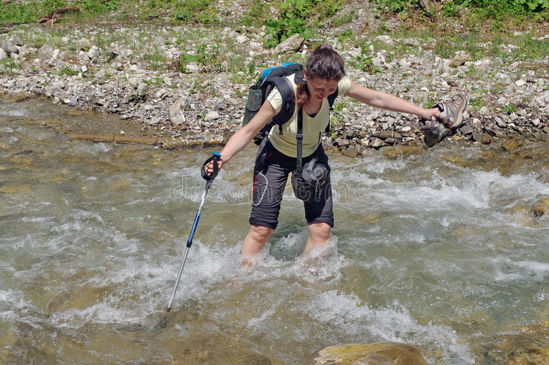 Mountain river. Young woman crossing the cold water stock photography