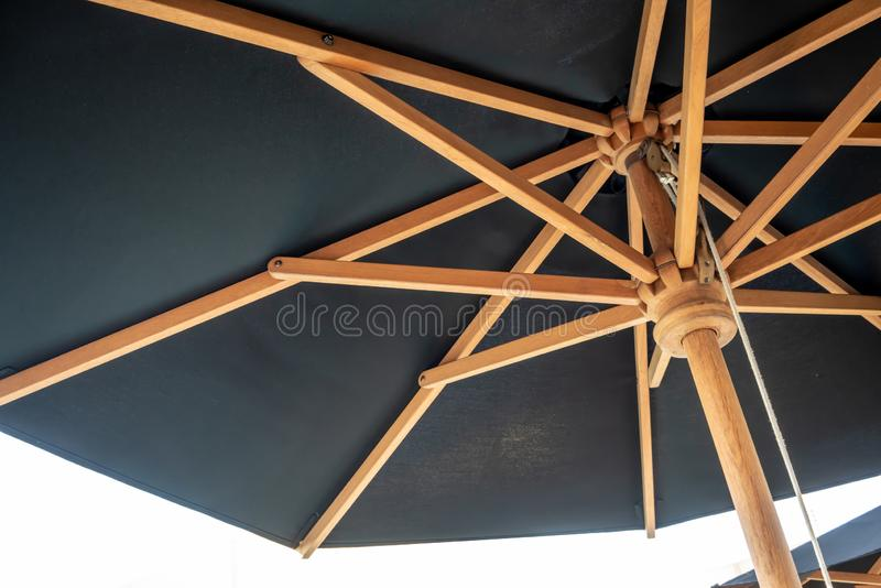 Crossing wooden umbrella structure create an abstract pattern on black stock photography