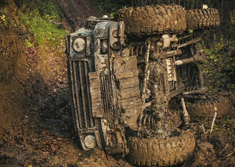 Crossover race on sunny day. Extreme entertainment concept. Dirty offroad car lies on side with forest on background. SUV rolled over on path covered with stock image