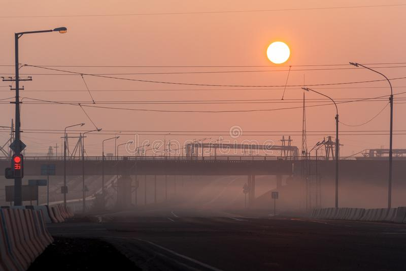 Crossroad, railway overpass and pillars in the fog at morning, N. Orilsk, August 23, 2018 royalty free stock photos