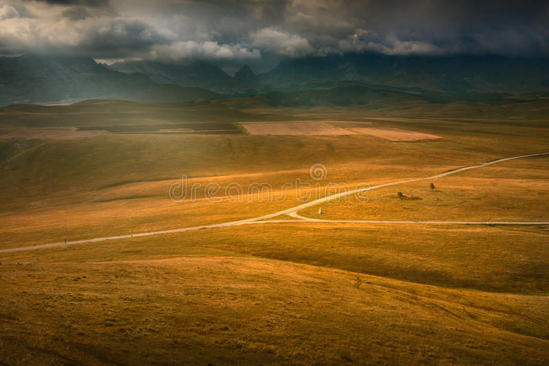 Crossroads of roads illuminated by sun rays on highland royalty free stock photos