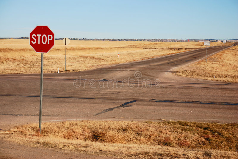 Crossroads (Stop sign). Have you ever been at a crossroads in life? Here we were, literally. A solitary intersection occupied by only stop signs and no one for stock image