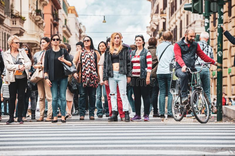 Crosswalk. Crowd of people waiting for the green light to cross the street. Rome, Italy. October 10, 2015: Crosswalk. Crowd of people waiting for the green stock image