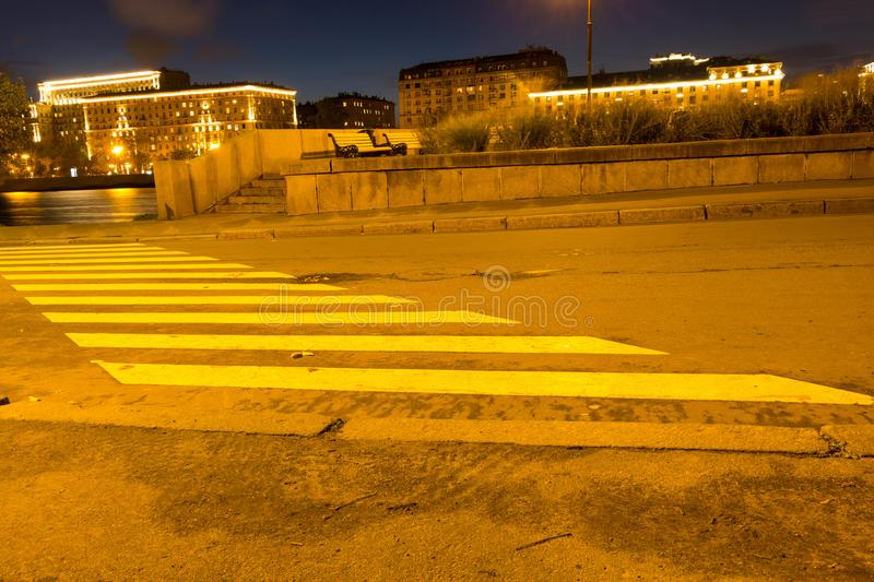 Crosswalk diagonally in a park in the evening in the lights royalty free stock photos
