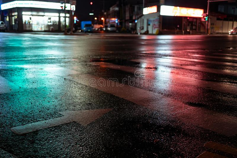 Crosswalk with pointing arrow in the night in neon light. Wet asphalt in red and green light royalty free stock images