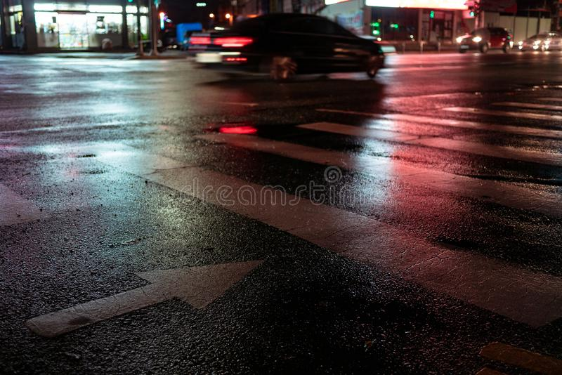 Crosswalk with pointing arrow in the night in neon light. Wet asphalt in red adn blue light. light trail from a passing car at night royalty free stock photo