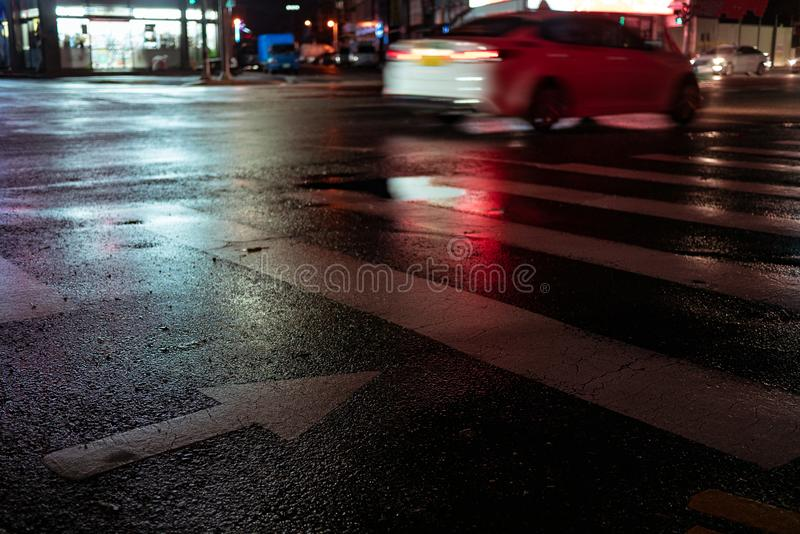 Crosswalk with pointing arrow in the night in neon light. Wet asphalt in red adn blue light. light trail from a passing car at night royalty free stock images