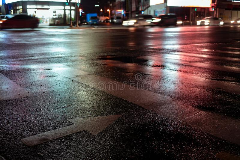 Crosswalk with pointing arrow in the night in neon light. Wet asphalt in red light. light trail from a passing car at night stock photography