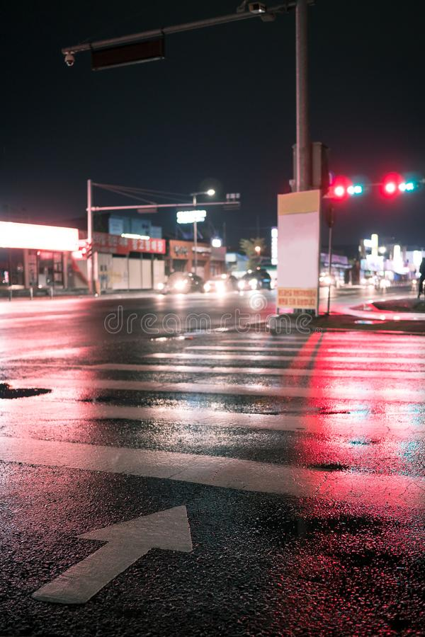 Crosswalk with pointing arrow in the night in neon light. Wet asphalt in red light. the traffic flow is in front of the red traffic light stock photo