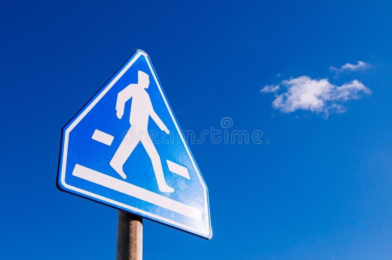 Crosswalk-voetgangersoversteekbord tegen blauwe hemel stock afbeeldingen