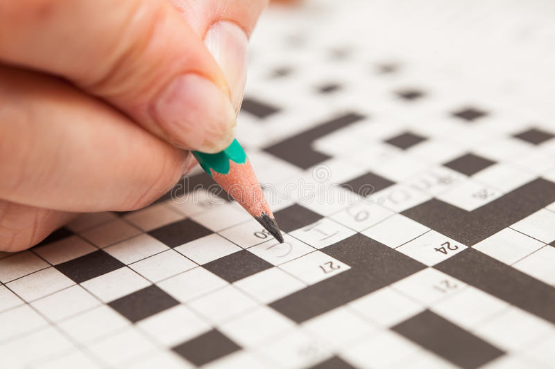 Crossword puzzle close-up. Hand doing crossword royalty free stock photography