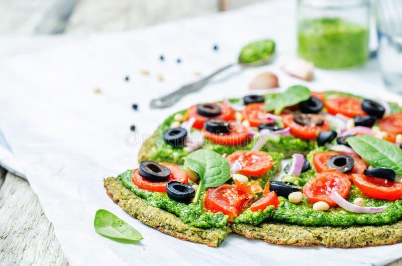 Crosta della pizza dello zucchini dei broccoli del vegano con il pesto degli spinaci, pomodori fotografie stock libere da diritti