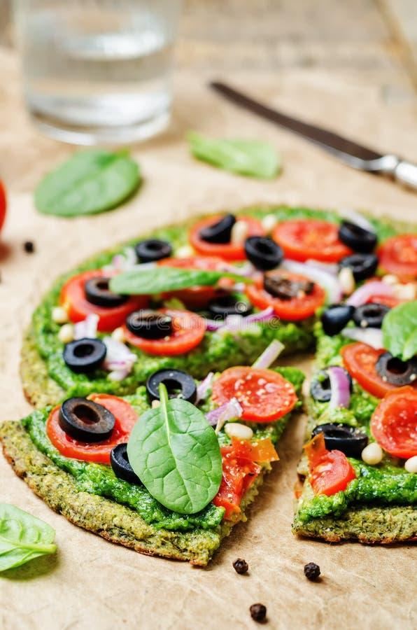 Crosta della pizza dello zucchini dei broccoli del vegano con il pesto degli spinaci, pomodori immagini stock libere da diritti