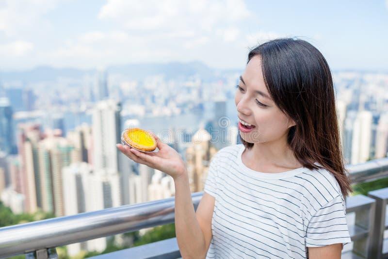 Crostata dell'uovo della tenuta della donna immagini stock libere da diritti