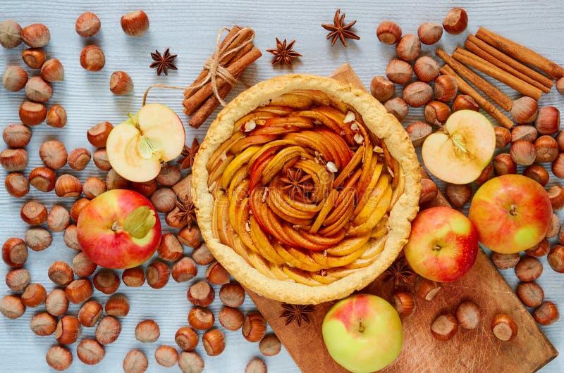 Crostata di autunno sul bordo di legno decorato con le mele, le nocciole e le spezie fresche - stelle e cannella dell'anice sulla fotografia stock