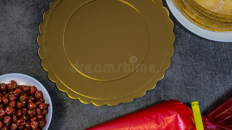 Crostata di ciliege casalinga, su una tavola di pietra, biscotti, borsa della pasticceria con crema, ciliege immagini stock