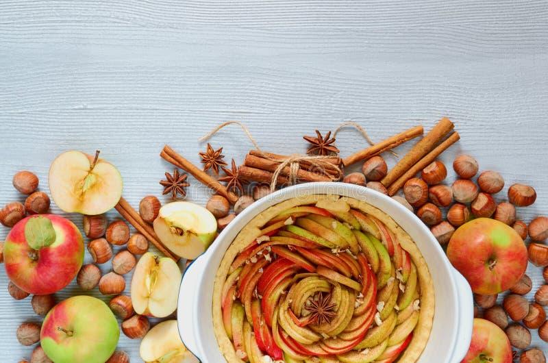 Crostata di mele cruda nel piatto di cottura decorato con le mele fresche, nocciole, bastoni di cannella, anice Dolce vegetariano immagini stock libere da diritti