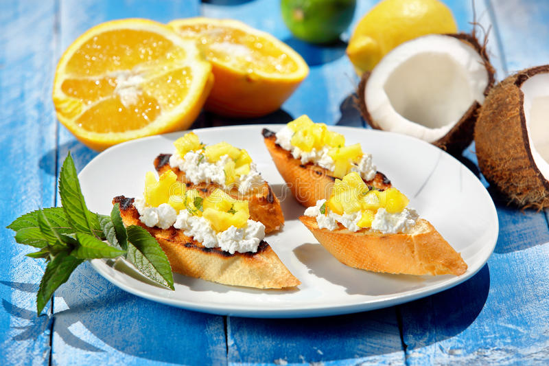 Crostini с ананасом на голубой деревянной предпосылке стоковые фотографии rf