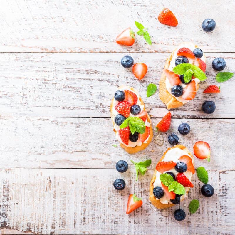 Crostini с зажаренными плавленым сыром багета, и ягодами стоковая фотография