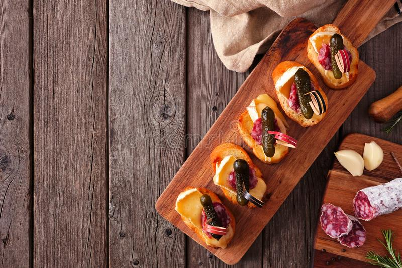 Crostini appetizer board with baked brie, sausage and pickles, top view serving scene over rustic wood with copy space royalty free stock photos