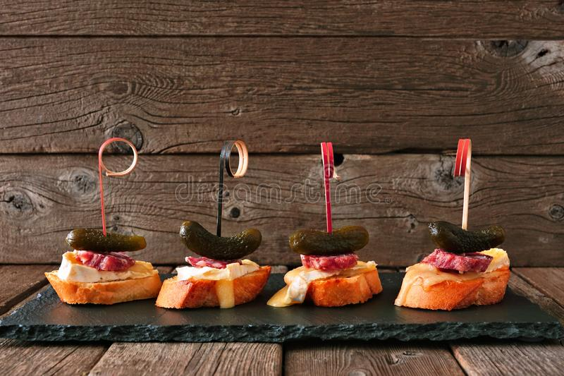 Crostini appetizer skewers with baked brie, sausage and pickles, serving platter against rustic wood stock images