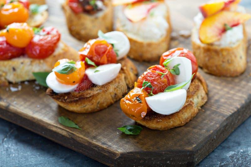 Crostini of bruschettaraad met caprese gemaakt met geroosterde tomaten stock afbeelding