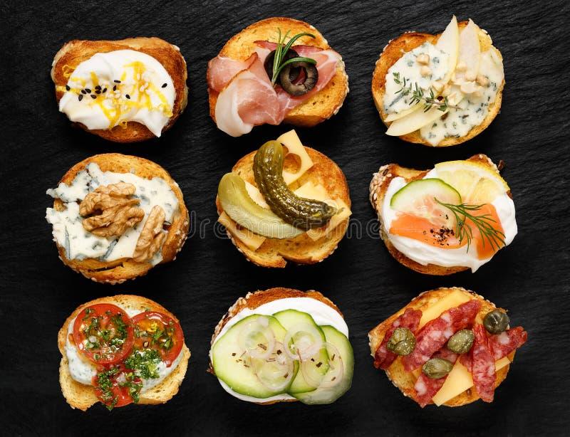 Crostini con diversos desmoches en los aperitivos deliciosos del fondo negro foto de archivo