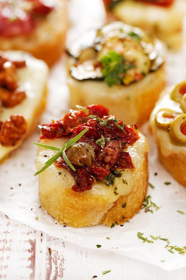 Crostini con l'aggiunta del pomodoro, della mozzarella, dei capperi e delle erbe seccati al sole immagini stock libere da diritti