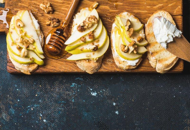 Crostini con la pera, el queso del ricotta, la miel y nueces foto de archivo