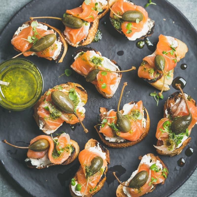 Crostini di color salmone casalingo con crema-formaggio, crescione, i capperi e il suace di pesto fotografia stock libera da diritti