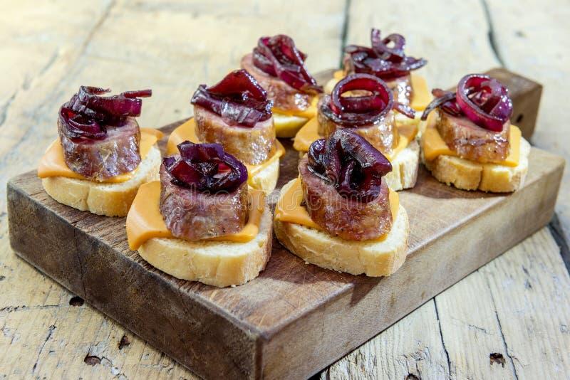 Crostini di pane con la salsiccia del formaggio e la cipolla caramellata fotografia stock
