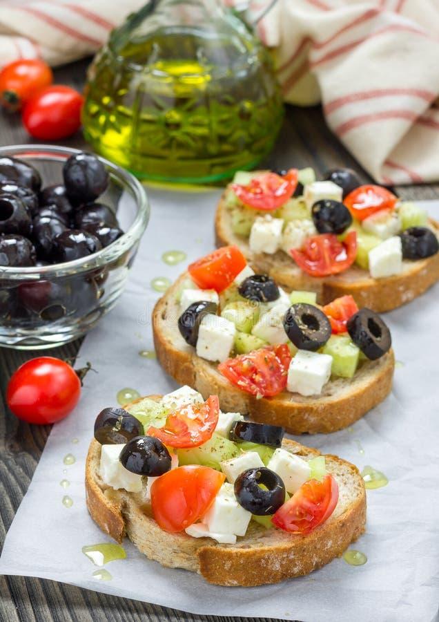 Crostini grego do estilo com queijo de feta, tomates, pepino, azeitonas, ervas imagens de stock royalty free