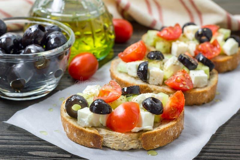 Crostini grego do estilo com queijo de feta, tomates, pepino, azeitonas, ervas fotografia de stock royalty free