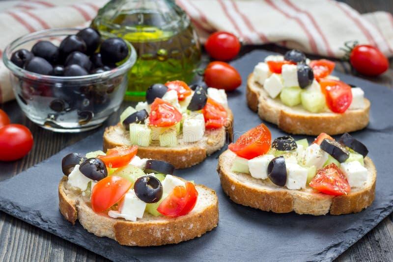 Crostini grego do estilo com queijo de feta, tomates, pepino, azeitonas, ervas fotografia de stock