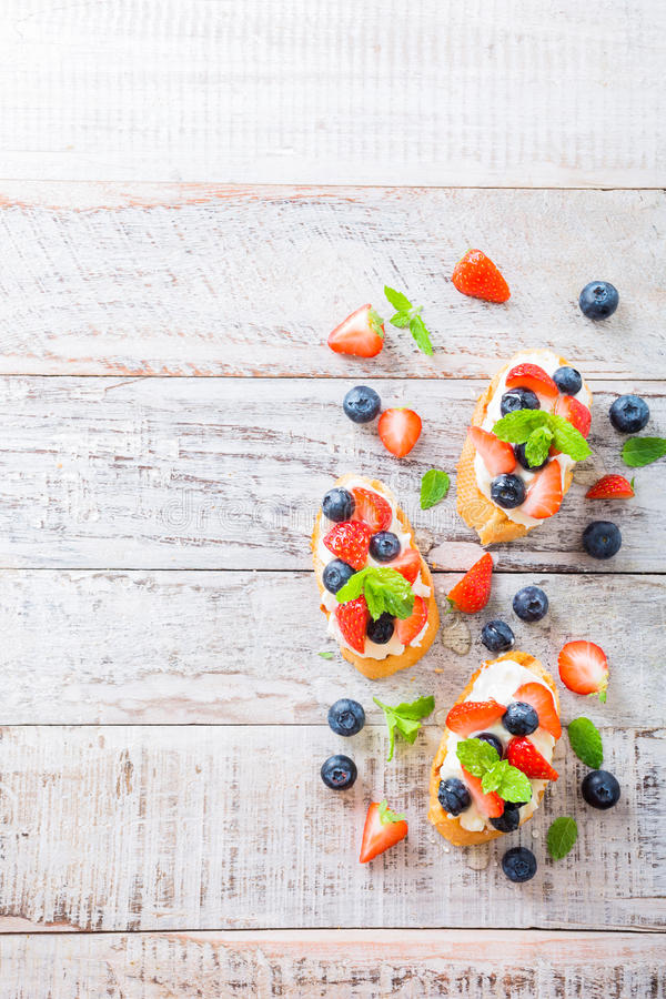 Crostini with grilled baguette, cream cheese and berries royalty free stock photography