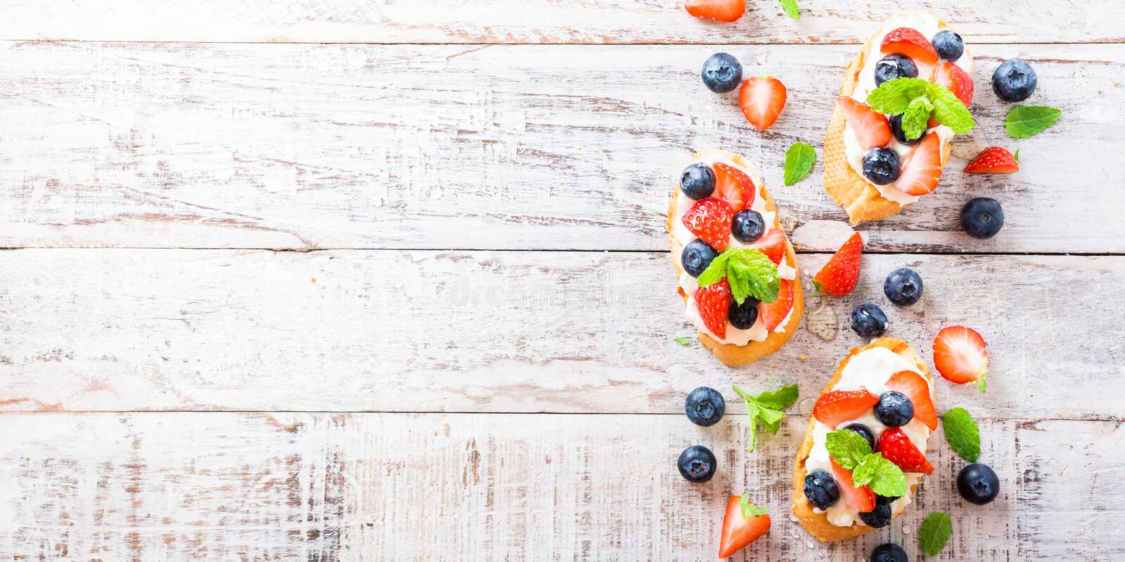 Crostini with grilled baguette, cream cheese and berries royalty free stock images