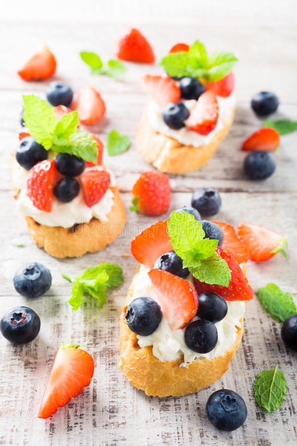 Crostini with grilled baguette, cream cheese and berries royalty free stock photo
