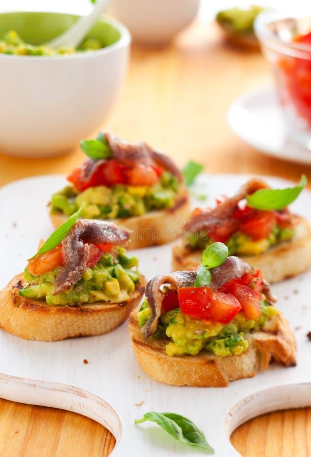 Crostini met avocado, tomaat en ansjovis stock foto's